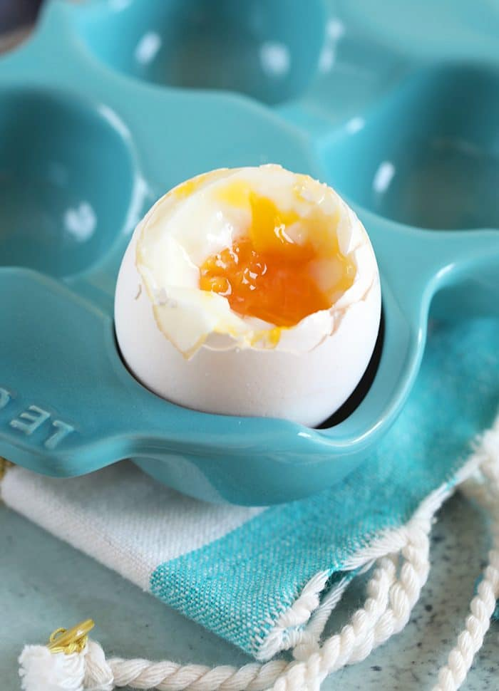 Soft Boiled egg with the top snipped off in an egg crate.