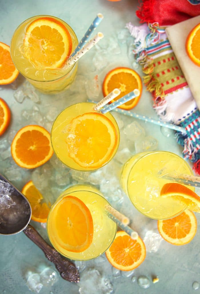 Overhead shot of three orange crush cocktails with orange slices and crushed ice on a blue board.