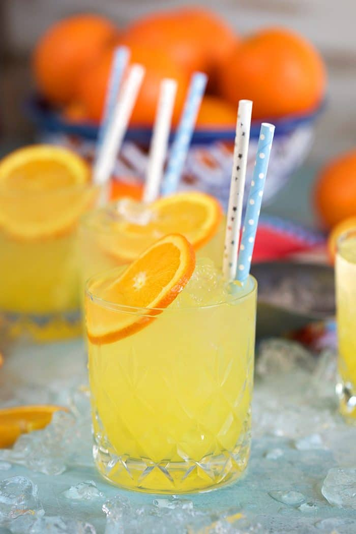 Famous Orange Crush Cocktail on a blue background with oranges in the background, and blue and white strawx.