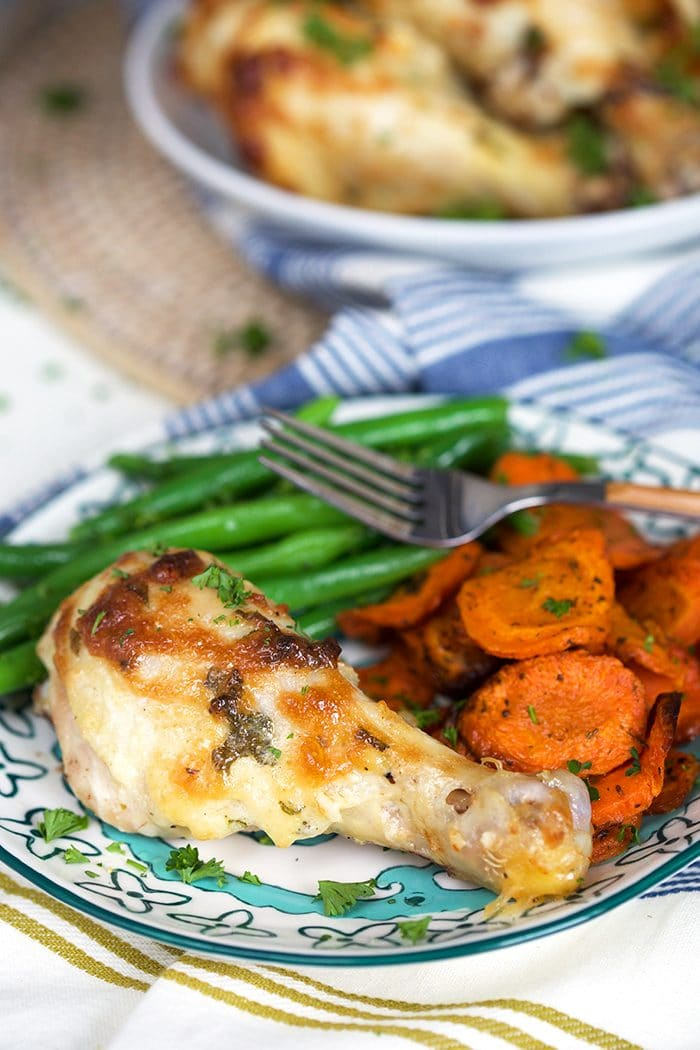 Baked chicken drumsticks on a plate with carrots and green beans.