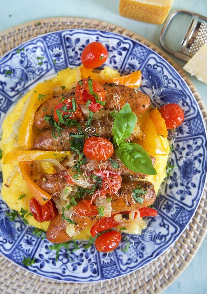 Overhead shot of Italian Sausage and Peppers with tomatoes and onions on a bed of parmesan polenta on a blue and white plate.