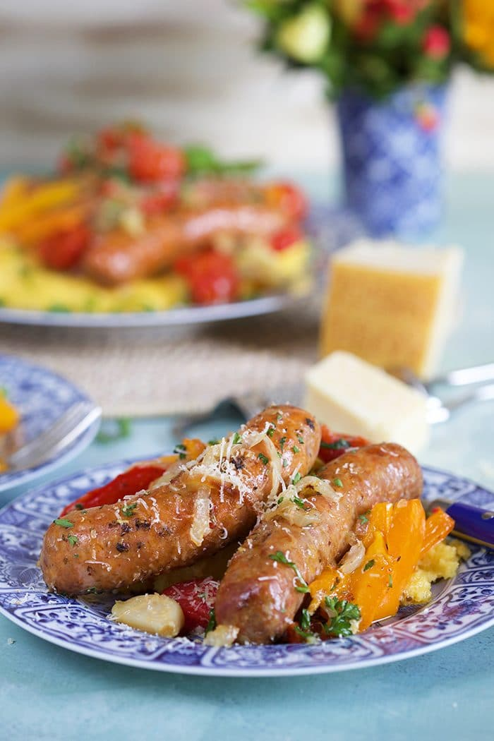 Two links of italian sausage and peppers with onions on a bed of polenta on a blue and white plate.