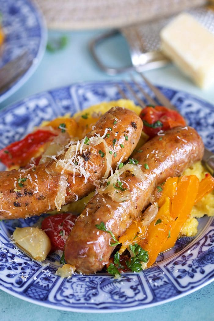 Italian Sausage and peppers on a bed of parmesan polenta on a blue and white plate with a wedge of parmesan in the background.