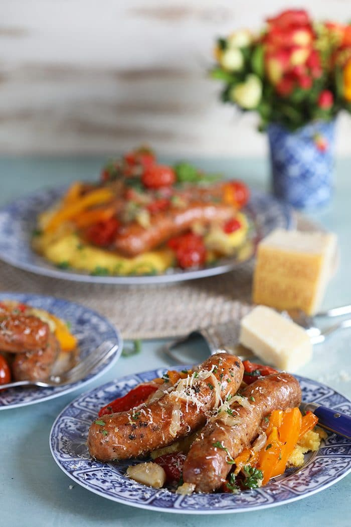 Italian sausage and peppers on parmesan polenta on a blue and white plate.