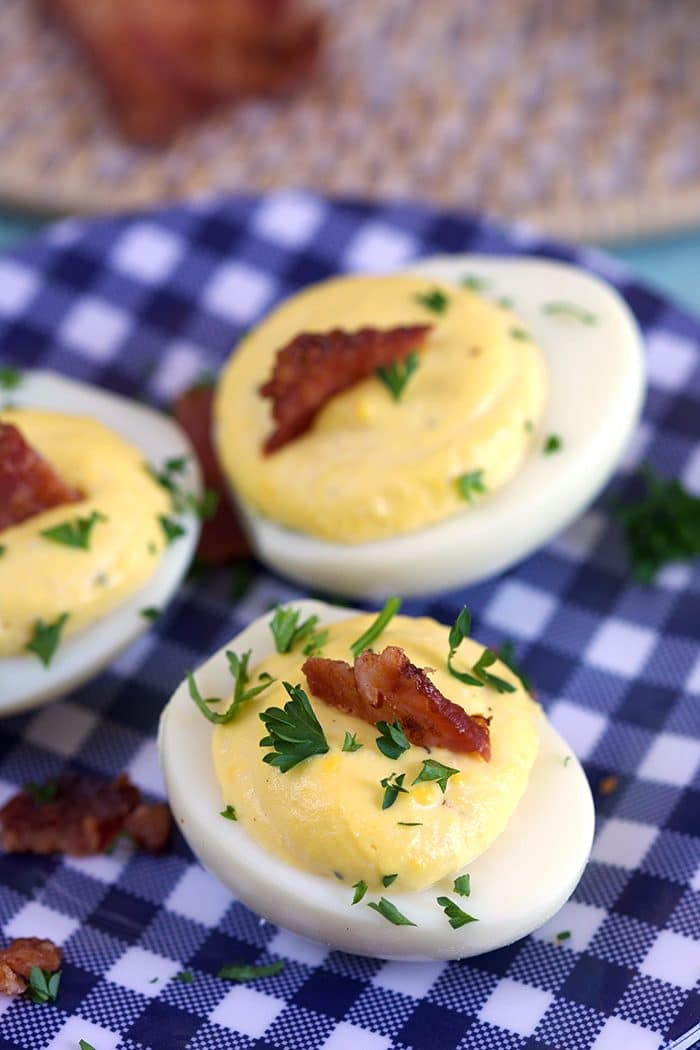 Bacon Horseradish Deviled Eggs on a blue and white gingham plate.