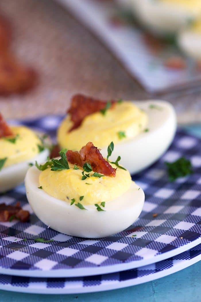Creamy deviled eggs on a blue and white gingham plate with a slice of bacon on top.