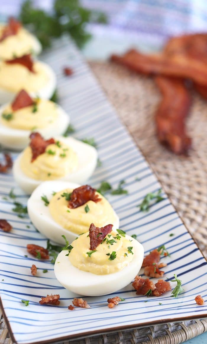 Bacon Horseradish Deviled Eggs on a blue and white rectangle platter.