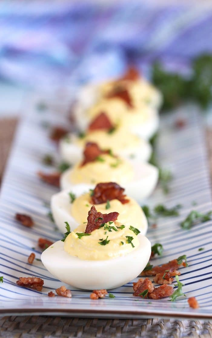 Bacon Horseradish Deviled Eggs in a row on a blue and white striped platter.