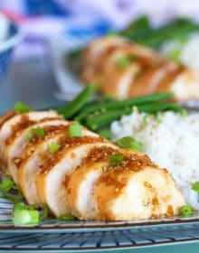 Sliced teriyaki chicken breast on a plate with rice.