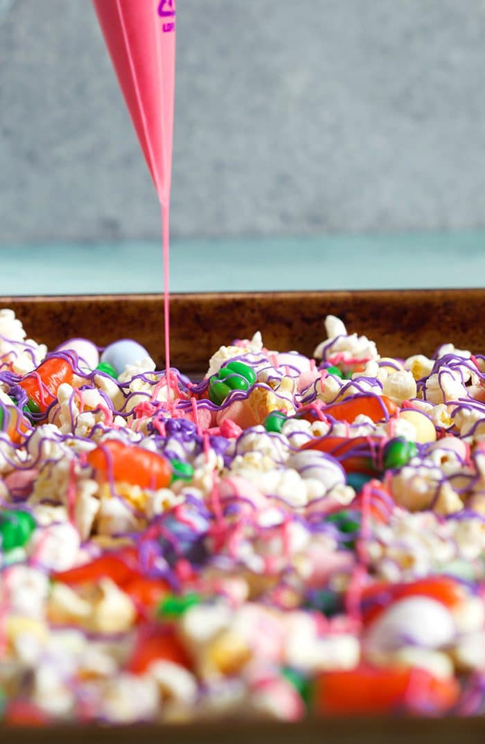 Bunny Bait Trail Mix in a Sheet Pan with pink chocolate being drizzled over it.