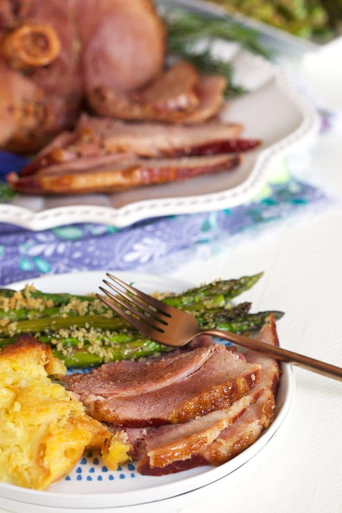 Slices of ham on a white plate with pineapple stuffing and asparagus.