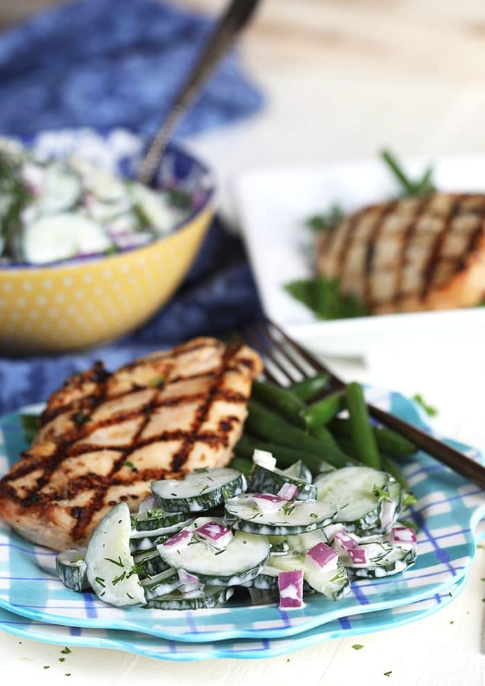 Creamy cucumber salad on a plate with grilled chicken breast.