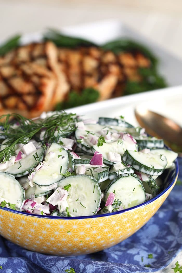 Creamy Cucumber Salad in a yellow bowl on a blue napkin.