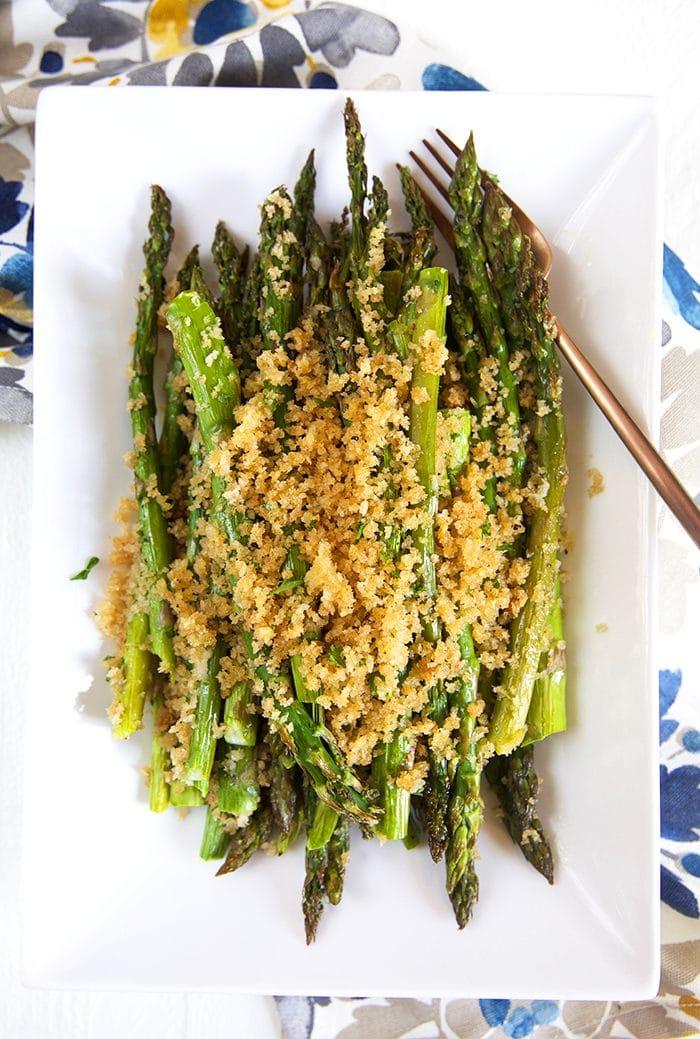 Overhead shot of baked asparagus on a white platter.