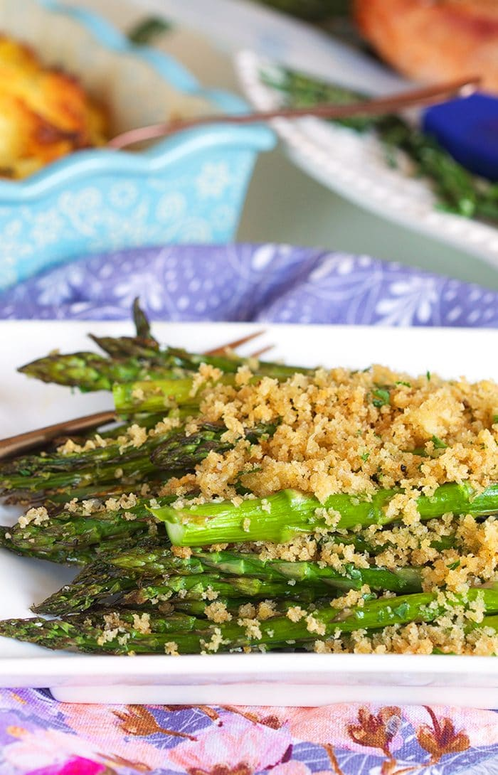 Baked asparagus with panko crust on a white platter.