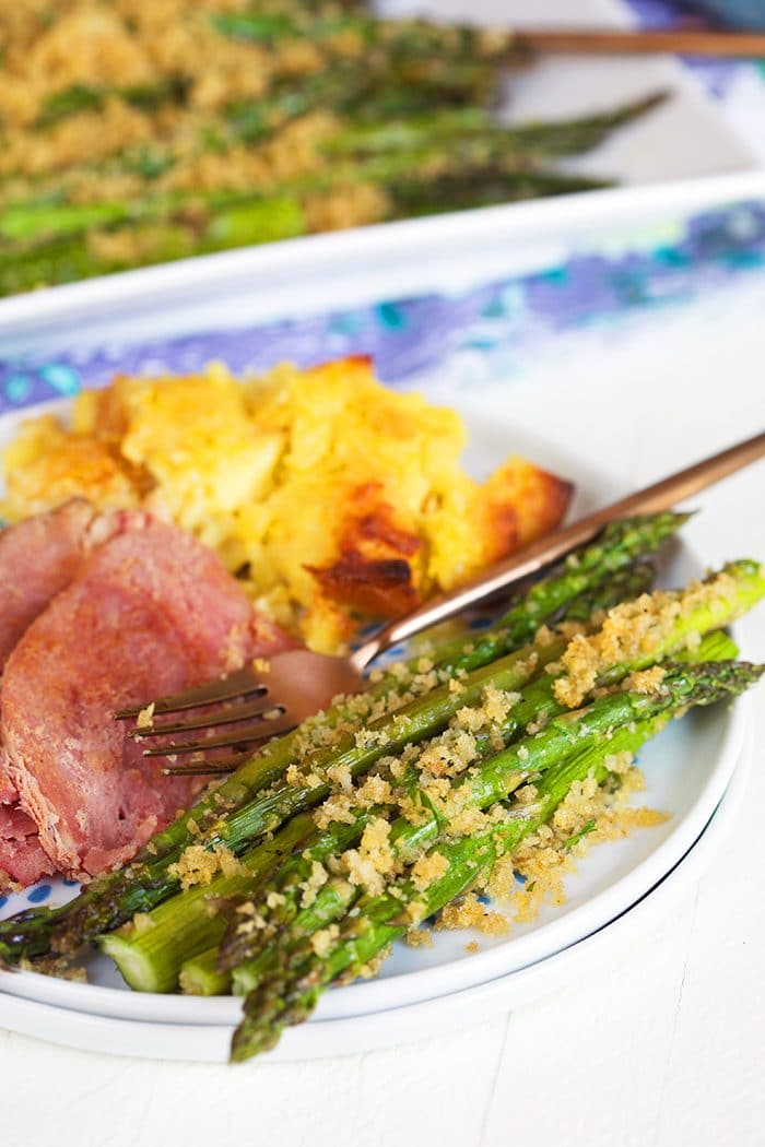 Baked asparagus on a plate with ham and pineapple casserole.