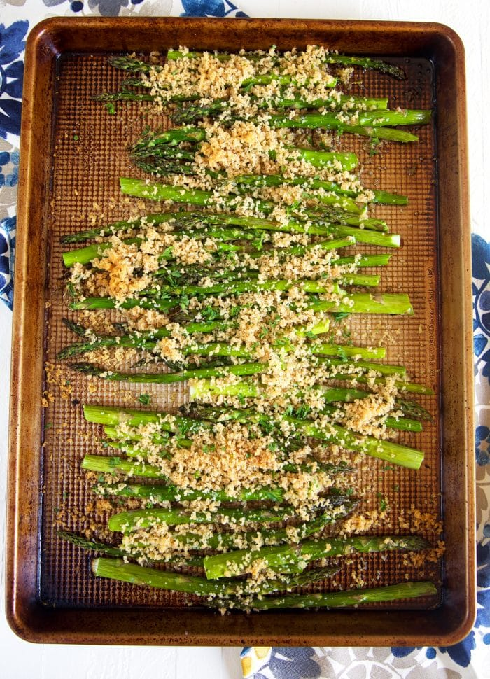 Overhead shot of baked asparagus on a baking sheet with panko crumbs.
