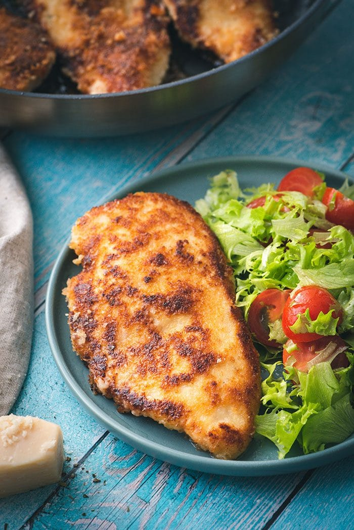 Parmesan Crusted Chicken on a plate with a small salad.