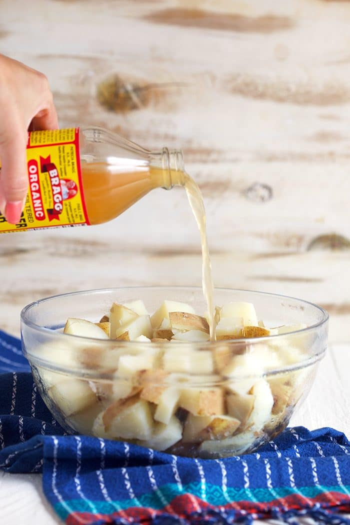 apple cider vinegar being poured over a bowl of potatoes.