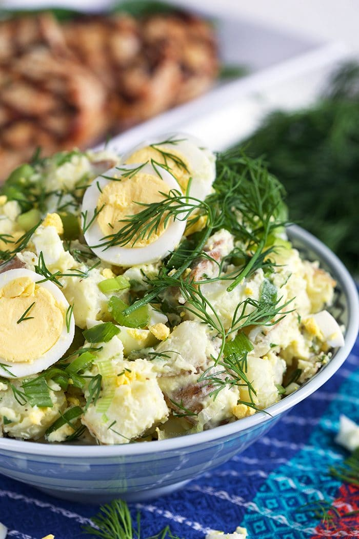 Potato salad in a blue and white bowl with dill and egg.