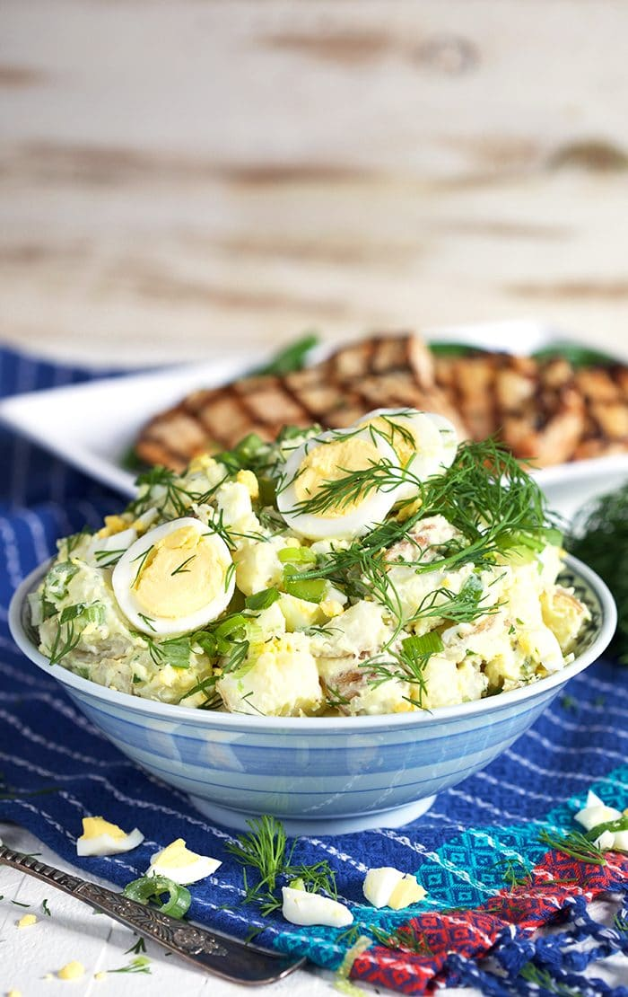 Potato Salad with egg and dill in a blue and white bowl.