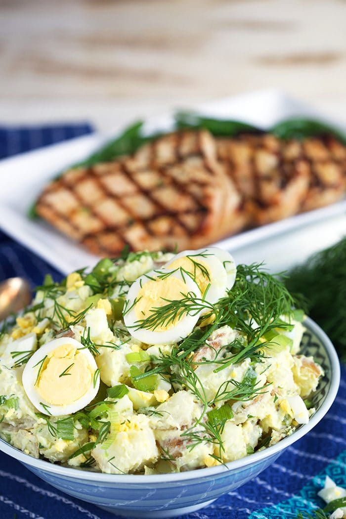 Potato salad with dill and egg in a bowl with grilled chicken on a plate in the background.