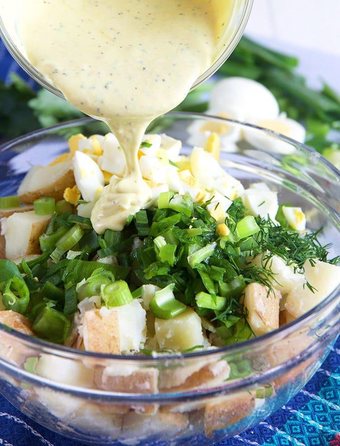 close up of potato salad dressing being poured over potato salad.