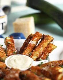 Zucchini Fries on a white platter with a wedge of parmesan and zucchini in the background.