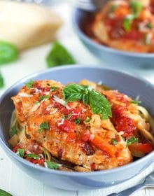 Chicken cacciatore in a blue bowl over pasta.