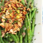 Green beans almondine on a rectangular white platter.