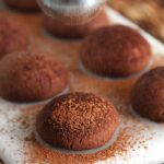 Cocoa powdered being dusted on a shortbread cookie.