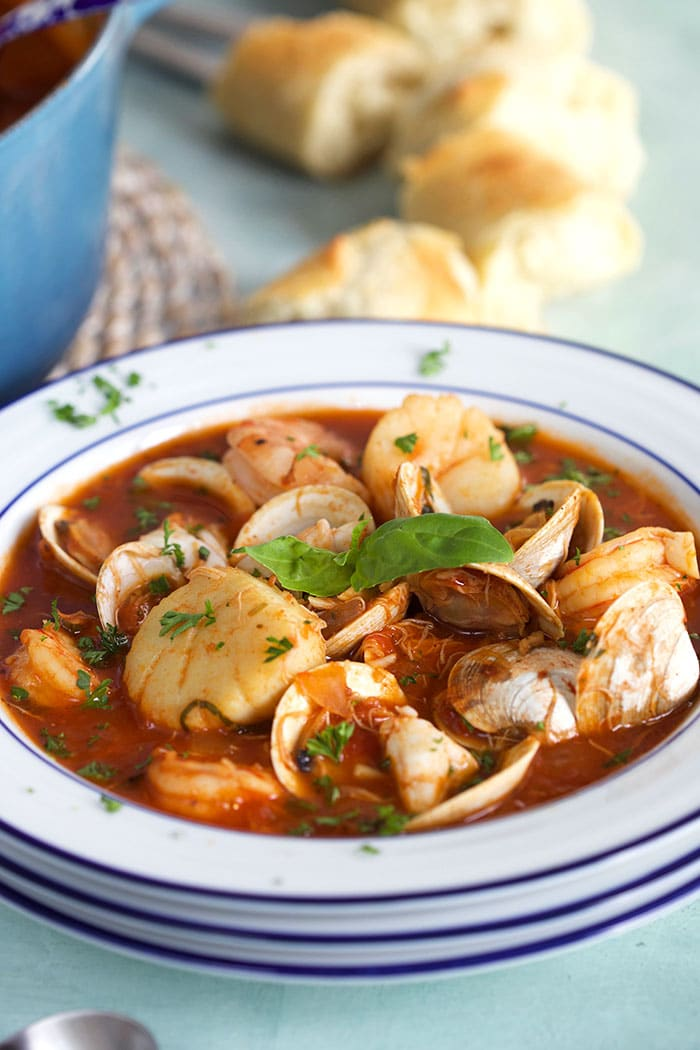 White bowl with seafood cioppino in it.
