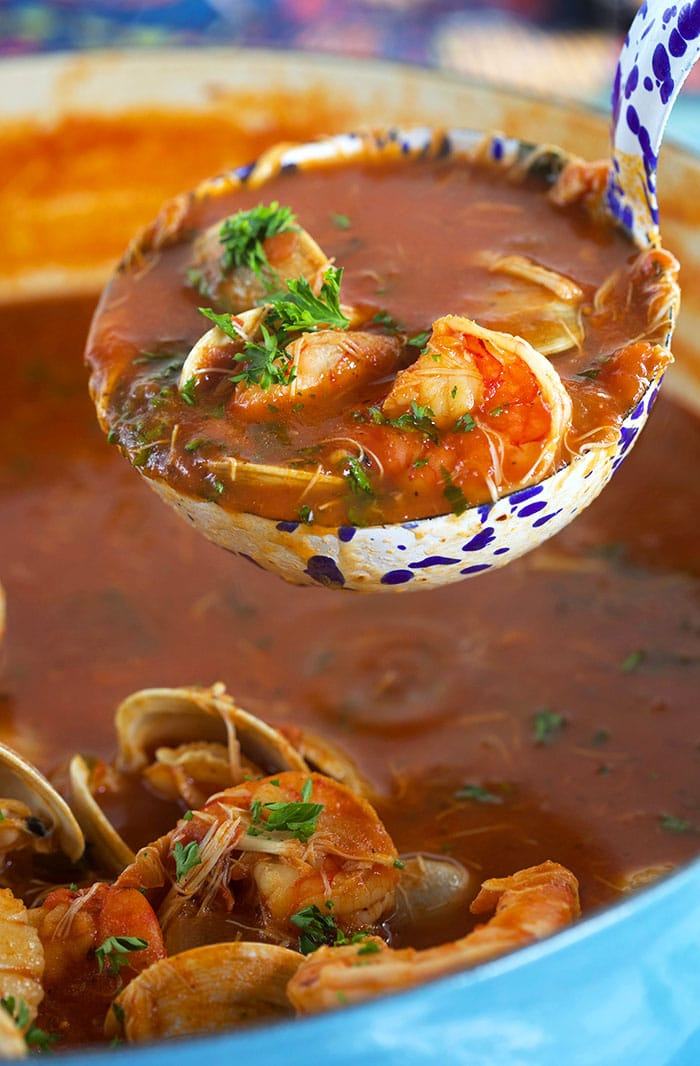 Seafood cioppino being served in a blue speckled ladle.