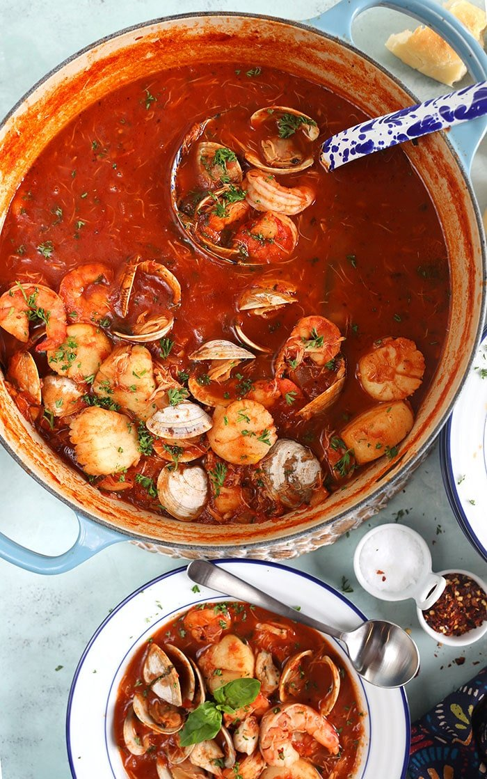 Overhead shot of seafood cioppino in a blue stock pot with a blue speckled ladle.