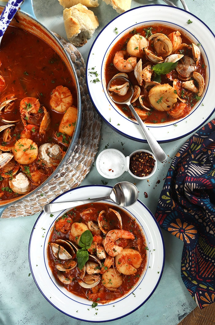 Overhead shot of seafood cioppino in white bowls on a blue background.