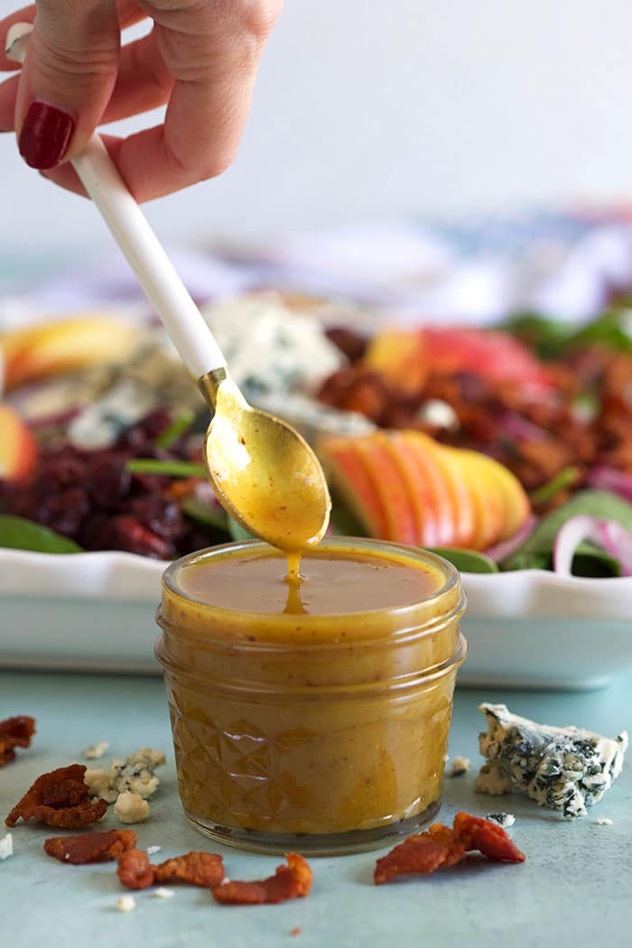 hot bacon dressing in front of a spinach salad with a white spoon drizzling dressing into the jar.