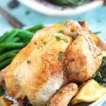 Close up of cornish hen on a white plate with a lemon wedge and green beans.