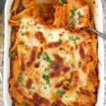 Overhead shot of baked rigatoni bolognese in a white baking dish on a blue background.