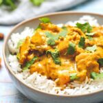 Butter Chicken in a bowl of rice with cilantro on top.