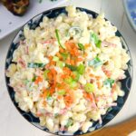 Overhead shot of macaroni salad in a blue bowl with a wooden spoon.