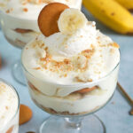 Close up of banana pudding in a small trifle dish with bananas in the background.