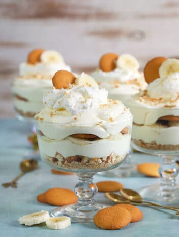 Banana Pudding in a small trifle dish with vanilla wafer cookies around on a blue background.