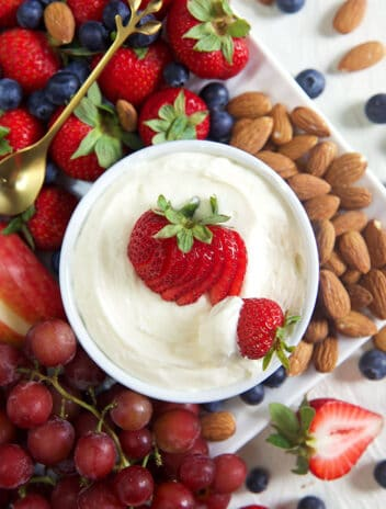 Overhead shot of a fruit platter with a bowl of marshmallow fruit dip with a strawberry on top.