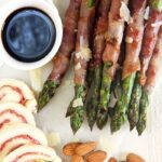 Overhead shot of prosciutto wrapped asparagus on a white board with sliced mozzarella pinwheels and almonds.