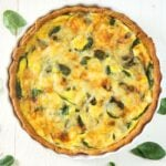 Overhead shot of Quiche Florentine on a white background with spinach leaves around it.