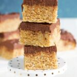 Scotcheroos stacked on a small cake pedestal.