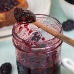 A jar is half filled with blackberry jam.