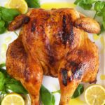 Overhead shot of spatchcock chicken on a white platter with lemons.