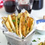 Parmesan Truffle Fries in a wire fry basket with parsley and a glass of wine.