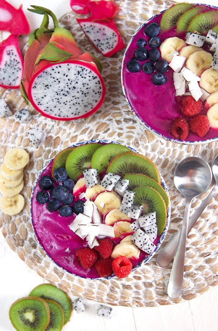 Overhead shot of two pitaya smoothie bowls on a wicker mat with a cut up dragon fruit on the side.